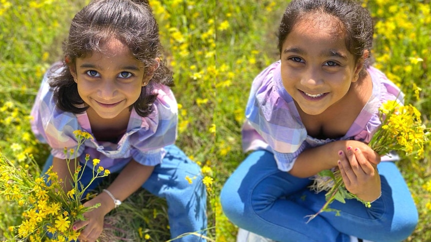 Kopika and Tharnicaa smiling, sitting in a field of green and yellow flowers.