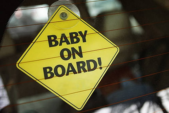 A baby on board sign in the rear window of a car to let motorists know to slow down.