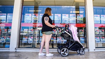 A woman stands with a pram looking at a large glass window with properties for sale pinned to it.