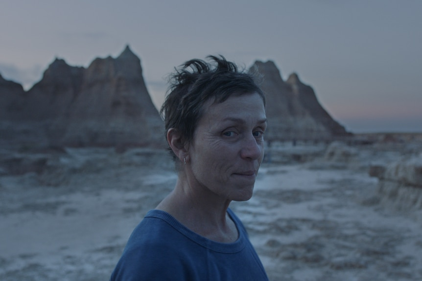 Twilight shot of the actress with pixie haircut and no make-up, wearing blue t-shirt, with arid mountain landscape in background