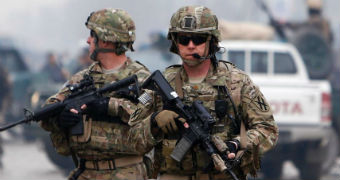 Two soldiers with high-powered weapons in camouflage gear patrolling