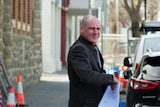 A bald man in a suit outside a court building