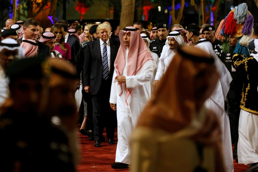 Saudi Arabia's King Salman and Mr Trump walk through a packed function room during a welcome ceremony at Al Murabba Palace