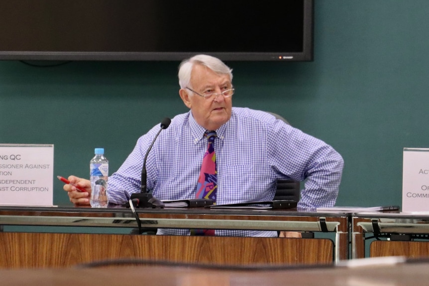 NT Anti-corruption commissioner Ken Fleming sits at a desk in NT Parliament, looking concerned.