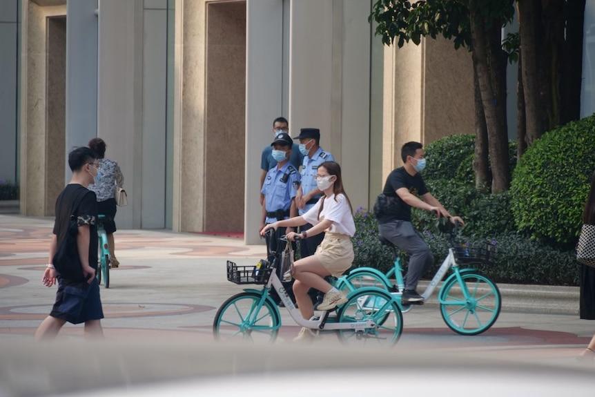 一个骑自行车的女人经过一栋大楼附近的一群警卫