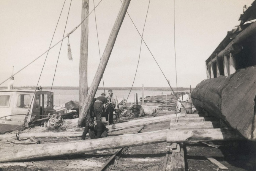 Historic image of men moving logs outside sawmill on waterfront