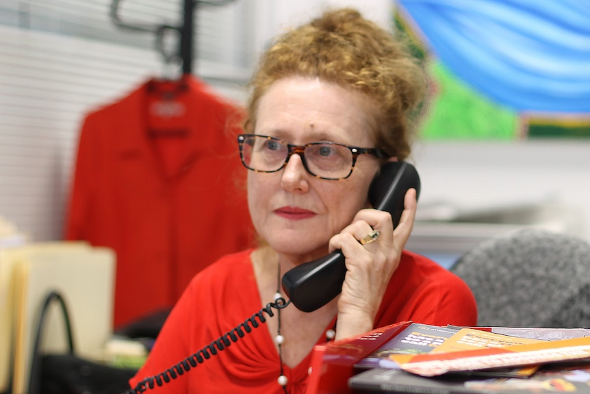A woman with red hair and spectacles on sits at a desk in an office holding a phone receiver to her face..