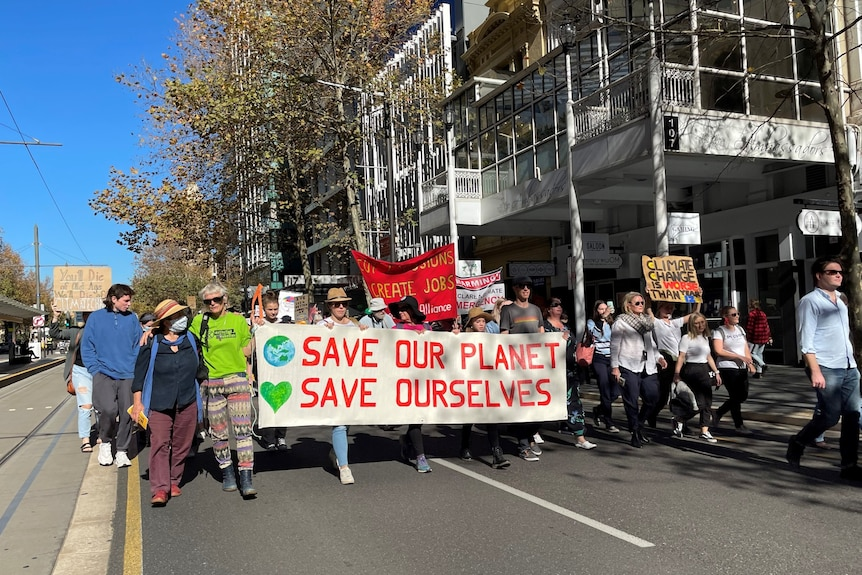 A group of protesters carrying signs and banners marches through Adelaide's CBD.