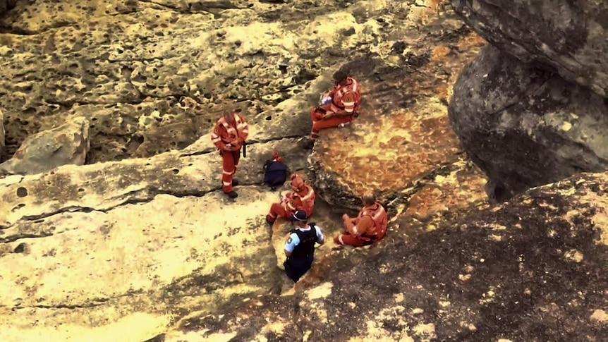 SES personnel and a police officer stand and sit on coastal rocks.