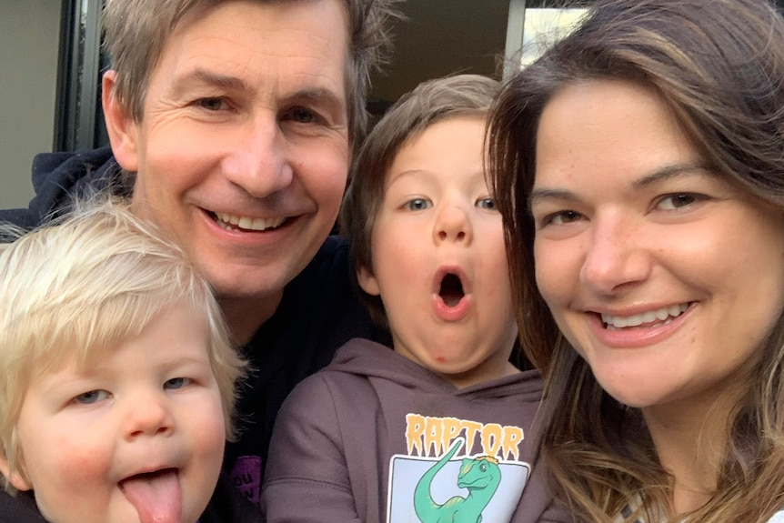 A family selfie of smiling man and woman, holding two small children who are pulling amusing faces.