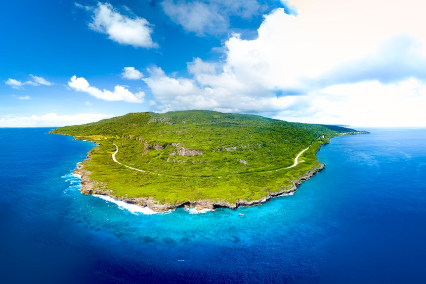 A bird's-eye photo of a small island on a clear day.