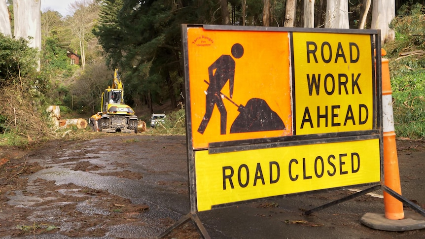 A 'ROAD WORK AHEAD' sign is laid out on a muddy road, with trucks visible further down.