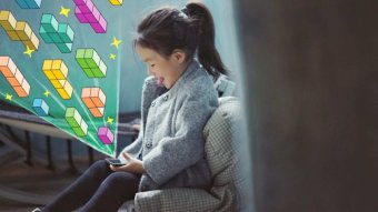 Little girl plays with phone with graphics of tetris coming out of it
