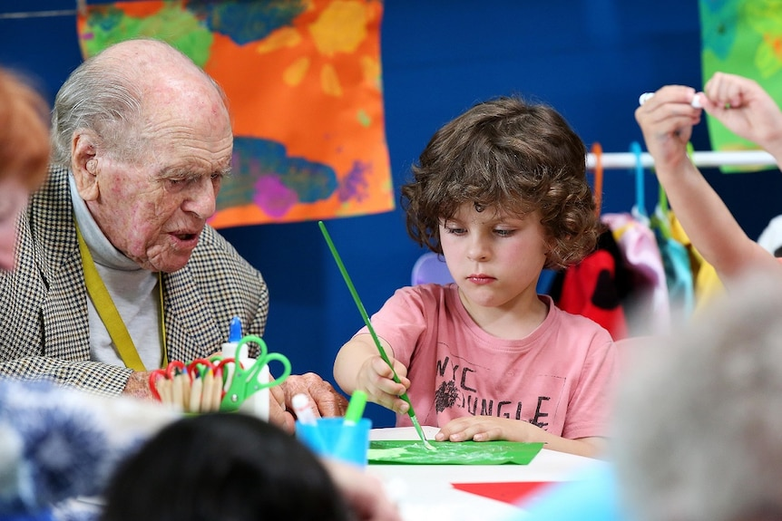 An elderly man in a tweed jacket watches a young child paint on the ABC TV series Old People's Home For 4 Year Olds.