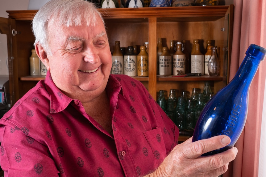 An older fellow smiles while looking at a blue antique bottle.