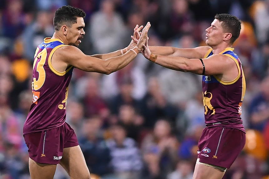 Two Brisbane Lions AFL players high five each other after a goal was kicked.