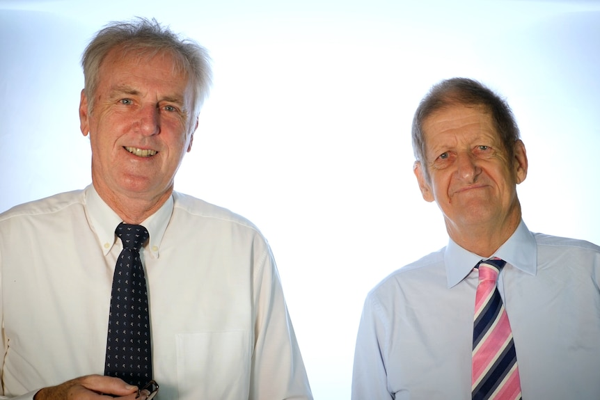 Roy Slaven and HG Nelson, wearing shirts and ties, stand in front of a white background.