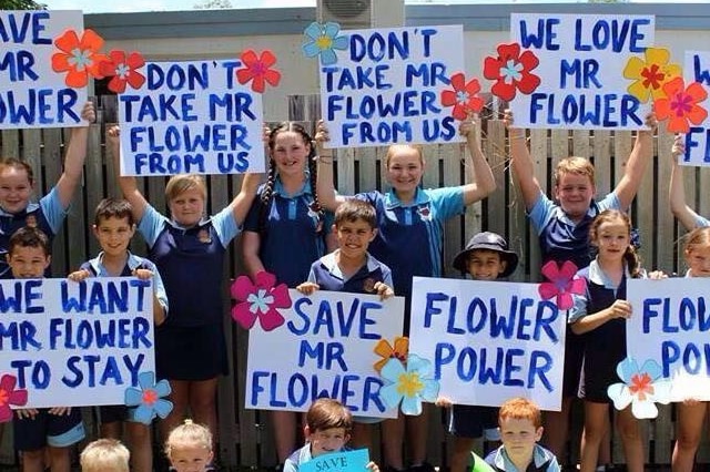 A group of school students stand together holding signs that read Don't take Mr Flower from us.