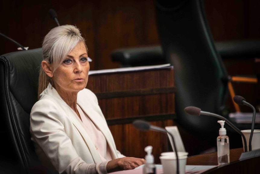 A middle-aged woman sits in parliament