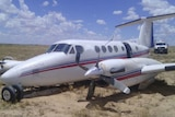 The Royal Flying Doctor Service plane that crash-landed in Moomba, showing bent propellers and damaged landing gear.