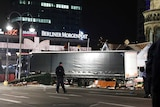 Police walk past truck at Berlin market