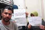 Abbas and his sister and mum holding signed to let them free because they feel like they are in prison but are innocent.