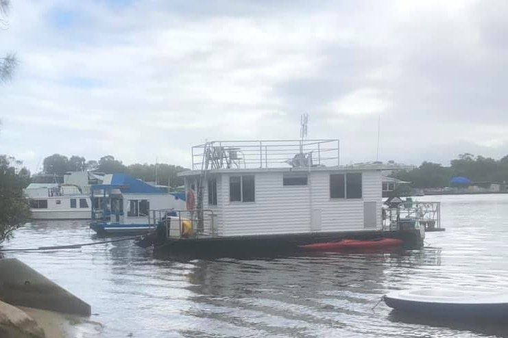 White houseboat with black hull anchored close to a small beach