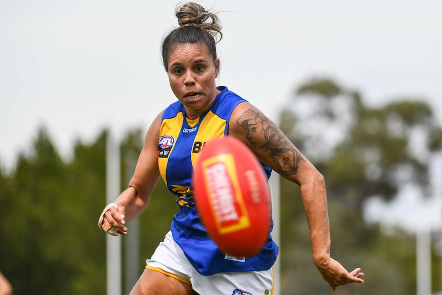 A woman in a West Coast Eagles blue and gold guernsey runs after an AFL football.