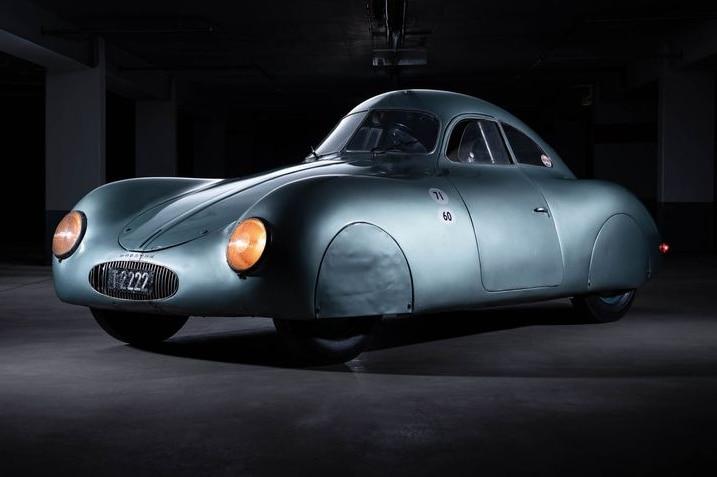 A metallic bubble-like car sits in a dark room.