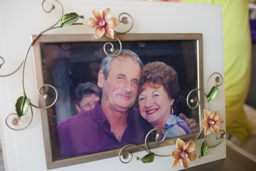 a man and woman smile in a photo that's been framed