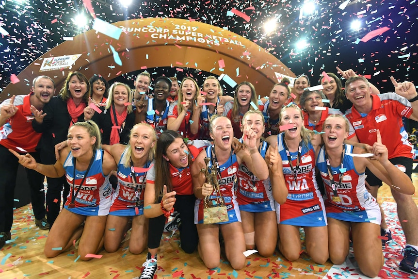 NSW Swifts players smile for a victory photo with a gold trophy