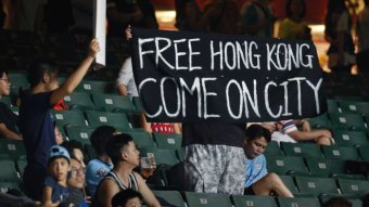 """Soccer fans hold a sign which reads """"Free Hong Kong Come on City"""""""