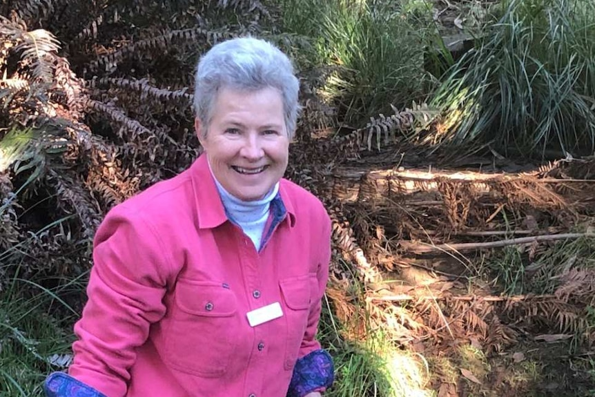 Fiona Marshall stands in a stream surrounded by bushland