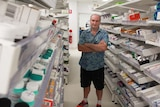 Man standing in a hospital pharmacy surrounded by rows of medicine