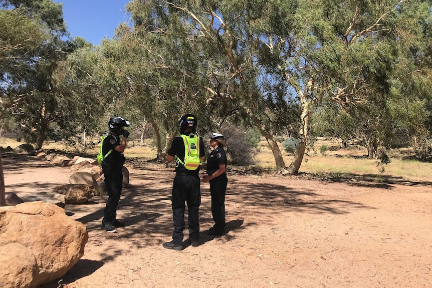 Three police officers stand near each other on red dirt near gum trees