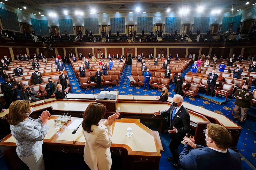 Joe Biden in a face mask gestures to Kamala Harris in the US House chamber in front of a small crowd