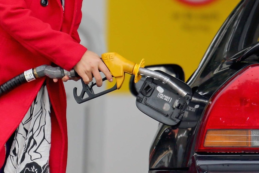 A woman uses a fuel dispenser to fill her car up with petrol at a petrol station.