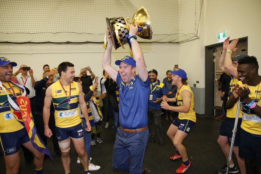 A man holds a large gold cup aloft while surrounded by football players.