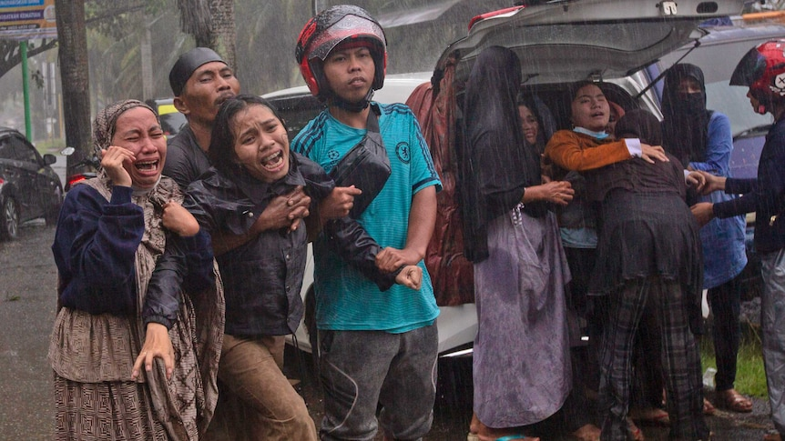 Women cry in despair as a body is recovered in the rain from under the rubble.