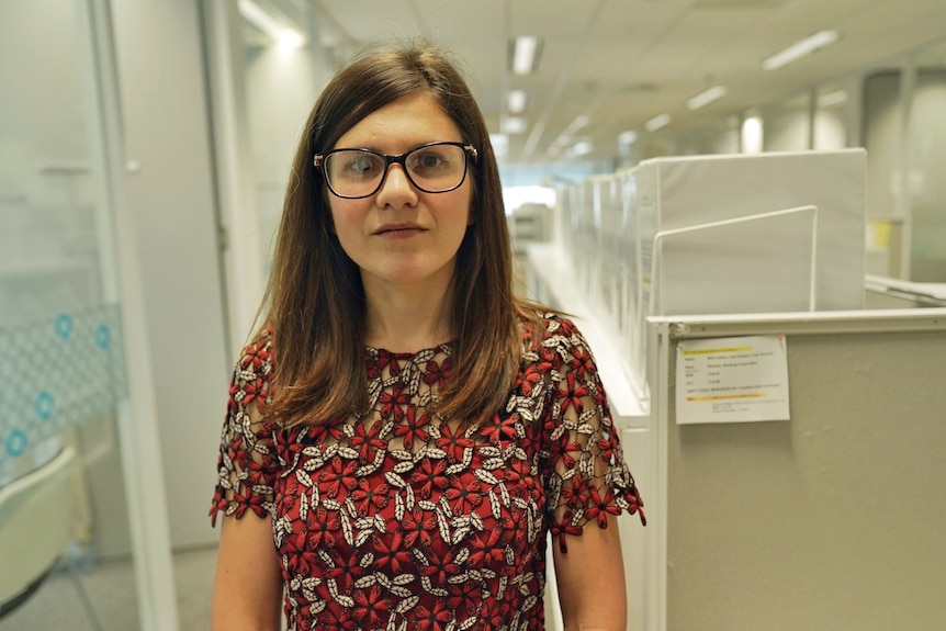 A woman stands in an office wearing a red dress and glasses.