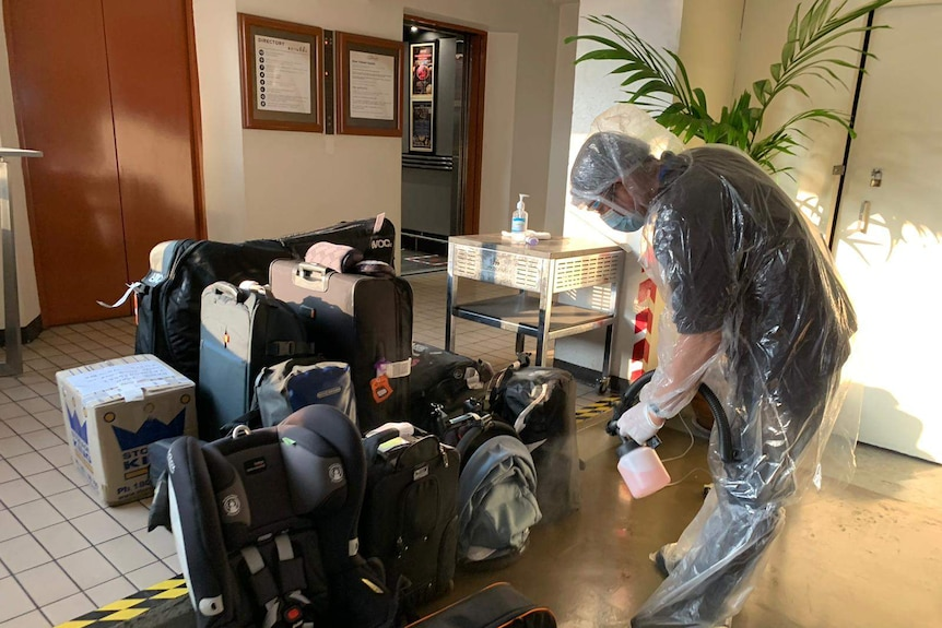 A man wearing a protective suit and face mask sprays down luggage in a lobby.