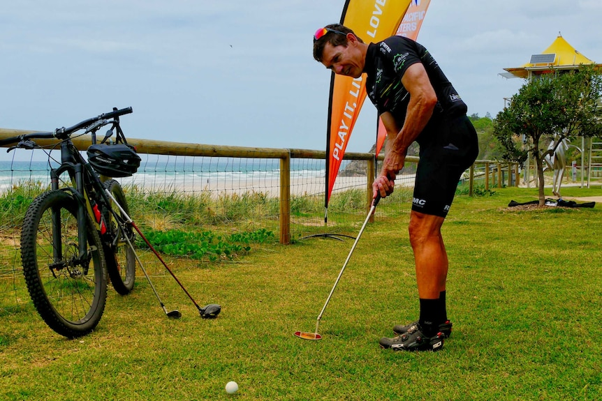 Man hits golf ball with mountain bike in the background