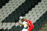 Two footballers compete for the ball in an empty stadium.