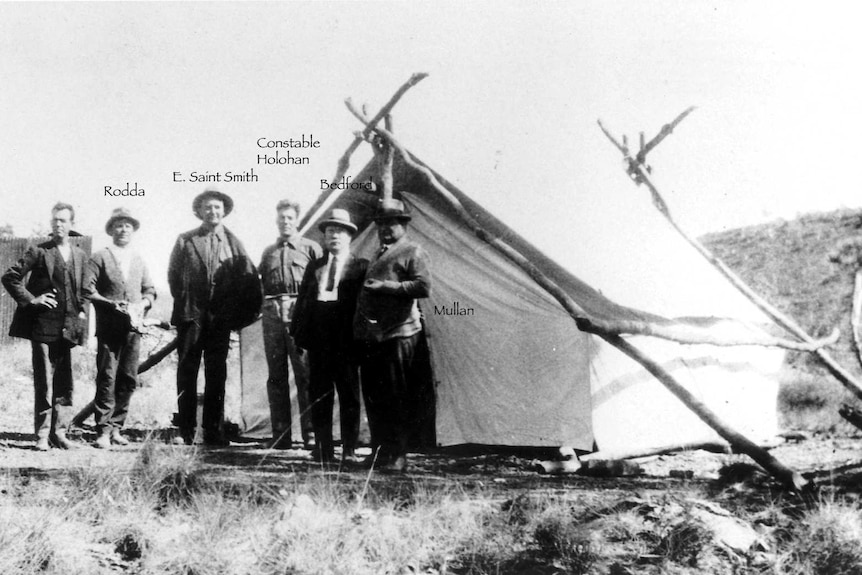 A small group of men stand in front of a white tent.