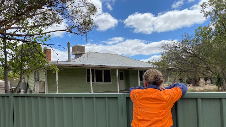Woman in high-vis shirt leans on backyard fence overlooking rundown weatherboard house, regional Victoria.