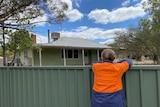 Woman in high-vis shirt leans on backyard fence overlooking rundown weatherboard house, regional Victoria.
