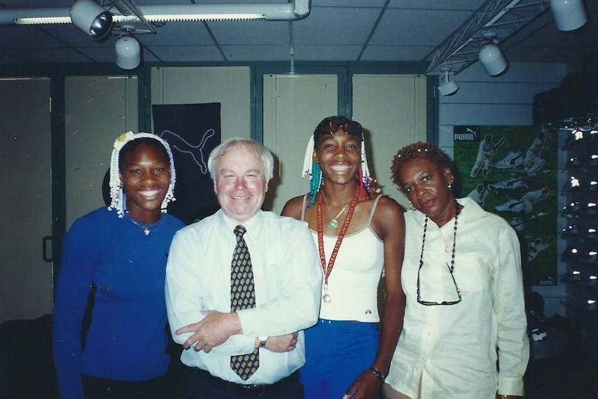 An older man stands smiling with Serena and Venus Williams and their mother.