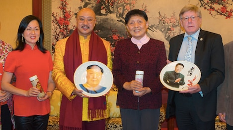 Woman in red, man in gold and red scarf holding plate, man in burgundy cardigan and man in suit and tie holding ornamental plate