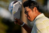 Hideki Matsuyama holds his hat and his putter