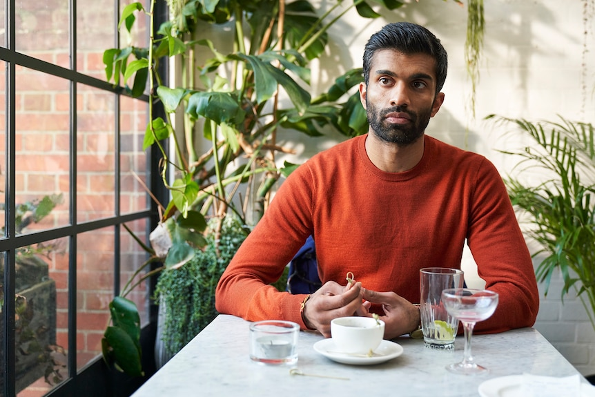 Nikesh Patel sitting at a cafe at lunch looking concerned, fidgeting with a skewer, in Starstruck